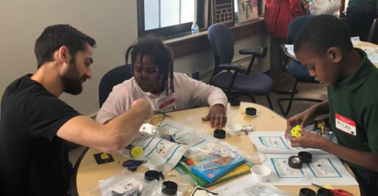 Detroit fourth-graders work with Hyundai Mobis engineer to build solar cars from kits.