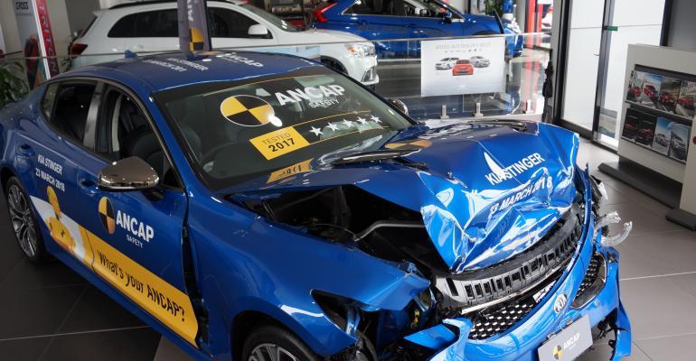 Crash-tested Kia Stinger on display on showroom floor.