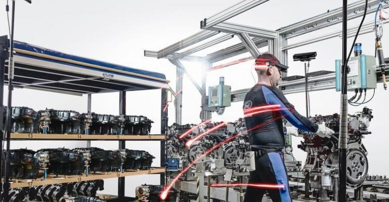 Ford Valencia Engine Assembly Plant worker wears special suit with sensors to help promote good posture.