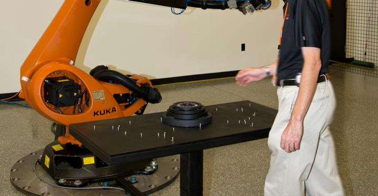 Kuka employee demonstrates safeoperations robotic cell