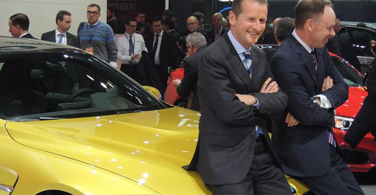 BMW board members Herbert Diess left and Ian Robertson rest on hood of allnew M4 coupe unveiled in Detroit