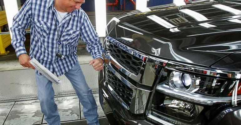 GM Arlington assembly plant employee Mark Magallon shines Chevy Tahoe badge