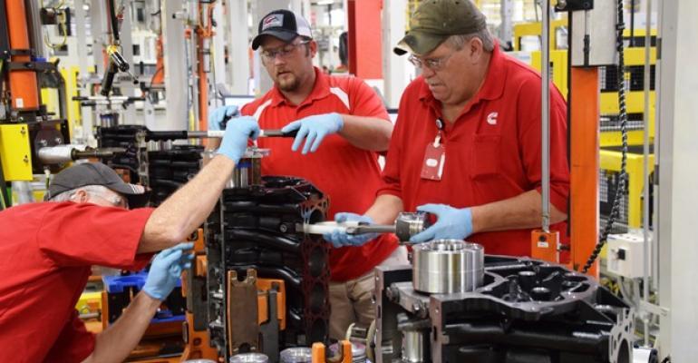 Cummins employee inserts piston in Nissan 50L diesel as part of pilot production