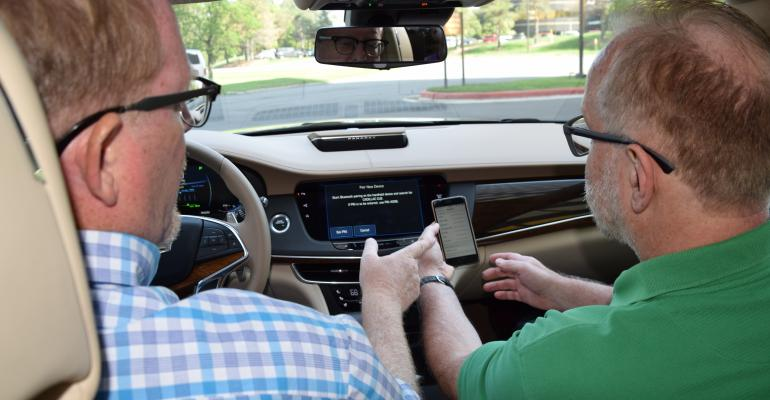 Editors Bob Gritzinger left and Drew Winter pair smartphone in Cadillac CT6