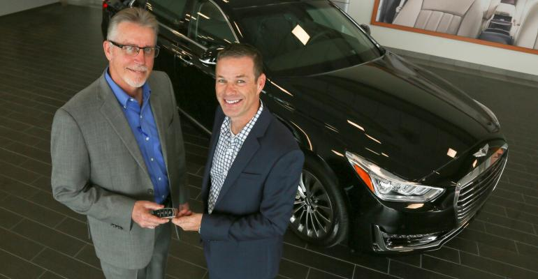 First rsquo17 Genesis G90 buyer Russ Johnson right takes keys from Michael Williams general manager of Round Rock Genesis in Round Rock TX