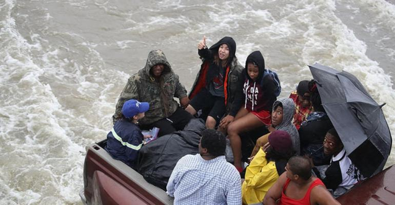 Flood evacuees ride in back of pickup truck Wednesday in in Port Arthur TX