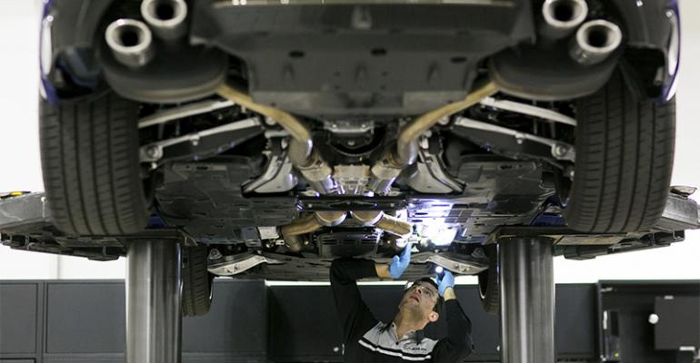 Lexus service technician inspects a vehicle for wear and tear