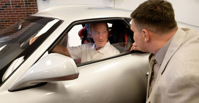 Purdue University President Mitch Daniels behind wheel of Keating Supercars Bolt as Keating founder Tony Keating looks on.