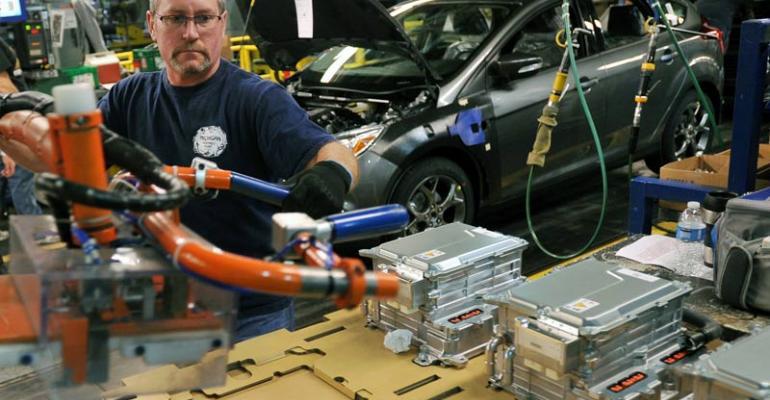 Mark Lynett installs battery in CMax hybrid at Michigan Assembly