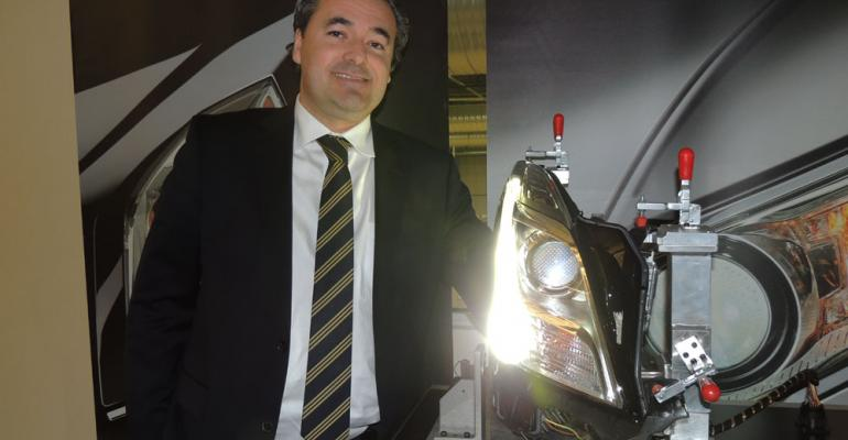 Steacutephane Veacutedie president and CEO of Automotive Lighting North America stands beside Cadillac XTS headlamp