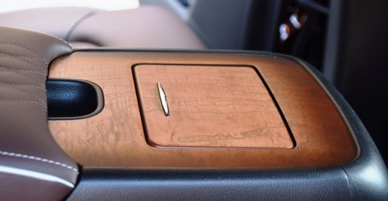 Spectacular wood trim extends to secondrow armrest of Infiniti QX80